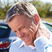 Man rubbing his neck after a car accident